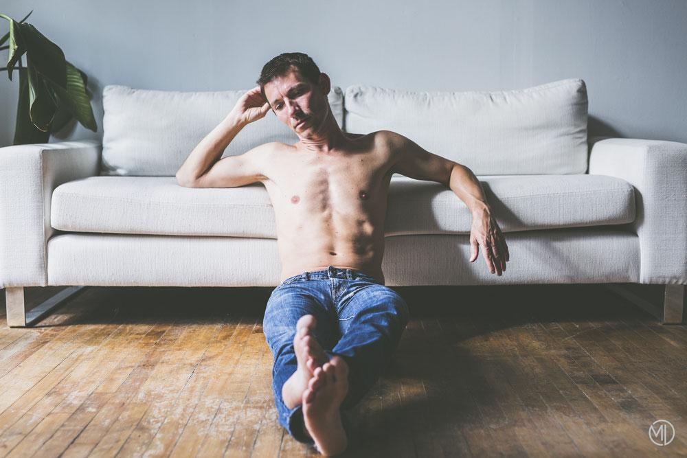 Photo boudoir homme blanc brun torse nu et jean bleu canapé sofa dans son salon à Montréal par Marie Deschene photographe