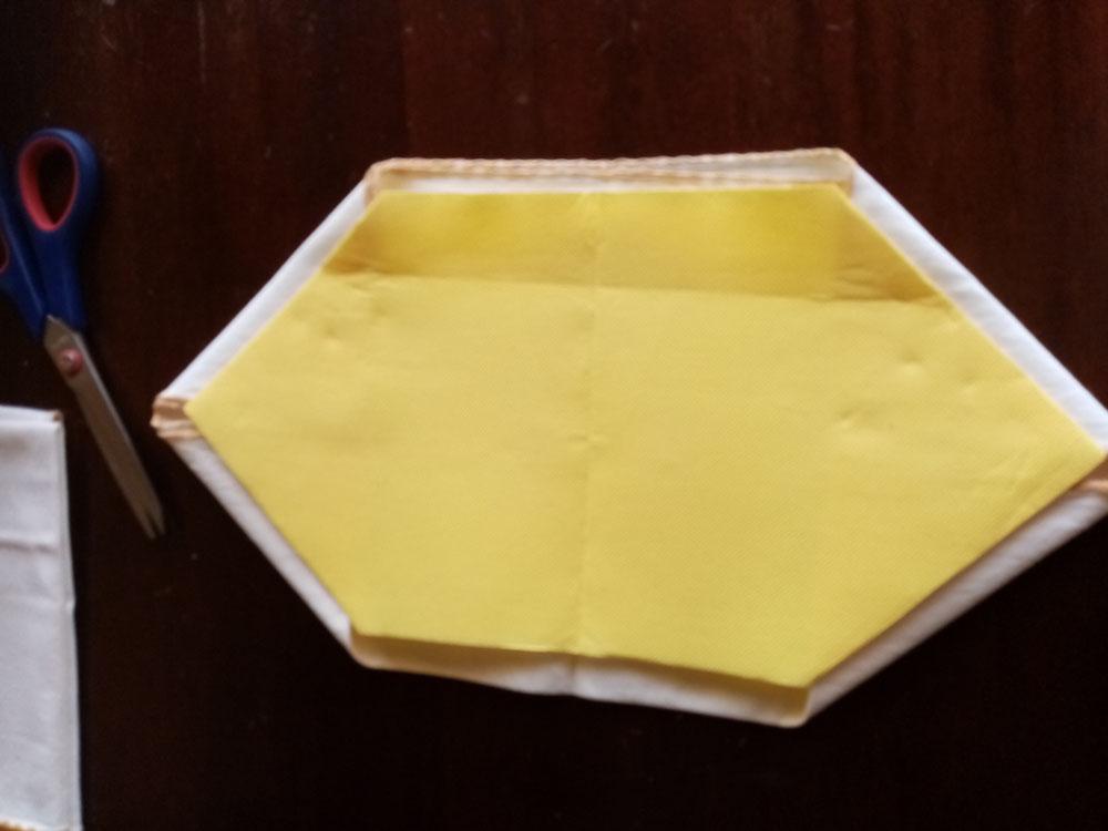 Ho messo il tovagliolo giallo con la parte delle piegatura rivolte verso il basso a contatto con l'altro tovagliolo, invece per quanto riguarda il tovagliolo sottostante la parte dei lati piegati è rimasto a contatto con il tovagliolo giallo