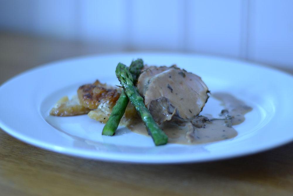 Timjanmarinerad helstekt fläskfilé och trattkantarellsås serveras med potatisgratäng och smörfräst sparris