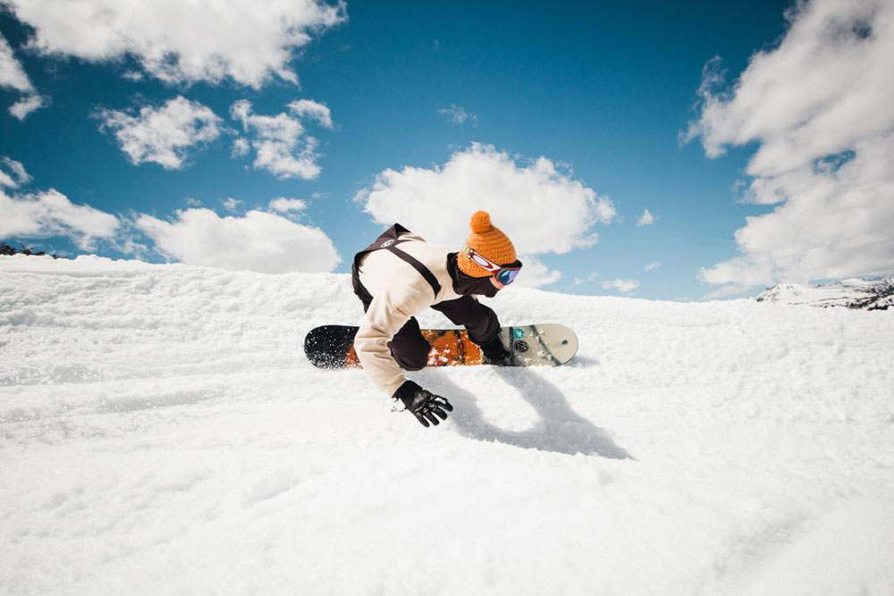Snowboarder carving on a berm