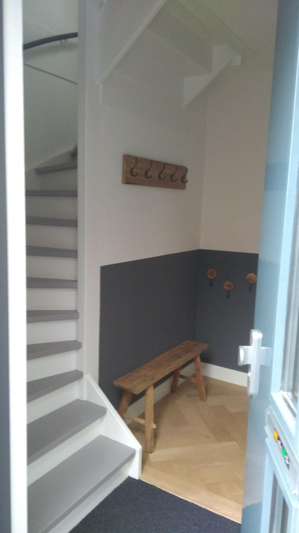 Entreehal met lambrisering, trap met zwevende treden. Alleen mooi als het strak is.