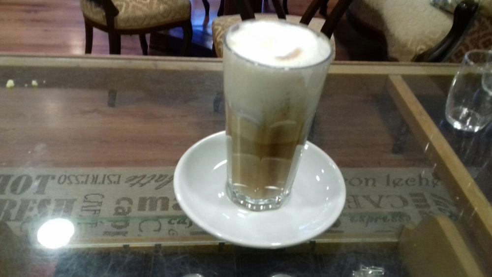 Lindau Café - Café Live in Lindau - Latte Machiatto in einem Glas auf einer Untertasse