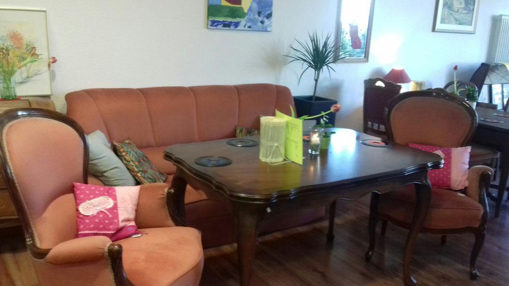 Lindau Café - Café Live in Lindau - feiern Sie Ihre Feste im Café, massiver Holztisch mit bequemen orangen Sitzgelegenheiten