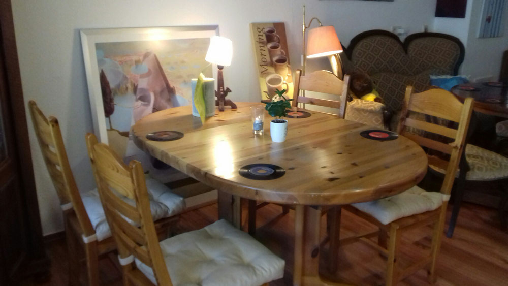 Café Lindau - Café Live in Lindau - Innenansicht des Ladens, Blick auf Holztisch mit Holzstühlen