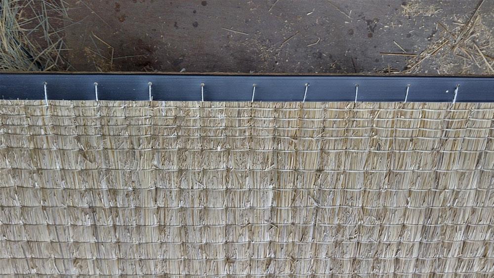 本床(藁床)にコーナー(補強材)を手縫いして、足で糸を締め込みました。