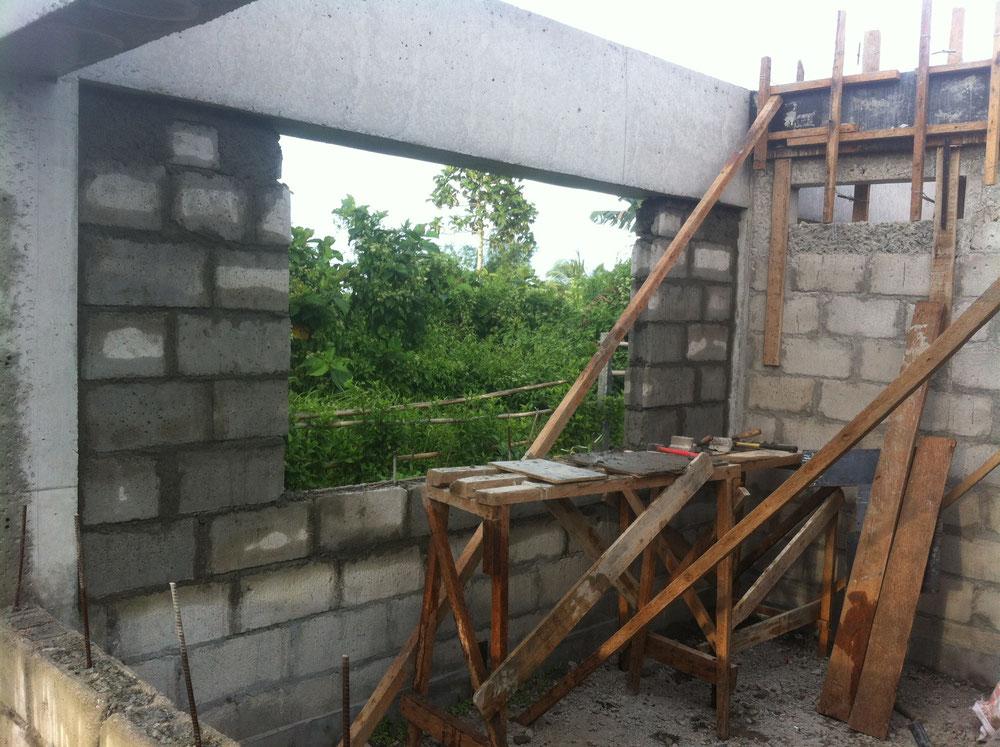 Eine frisch gemauerte Wand mit grossem Fenster und Gerüst