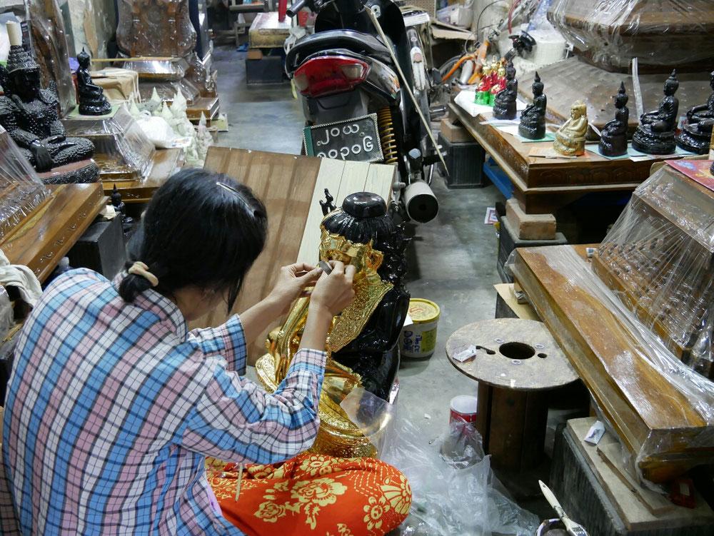 Frau beklebt den lasierten Buddah mit Blattgold
