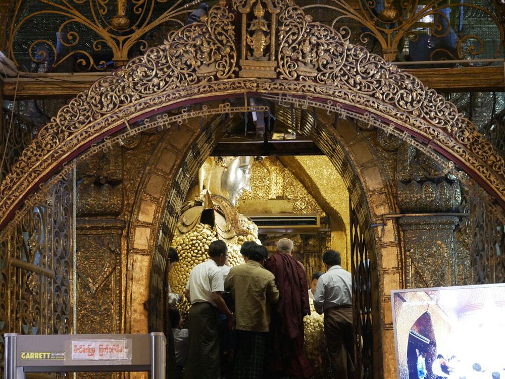 Die Männer beim bekleben. Das Gesicht des Buddhas ist die einzige Stelle ohne Blattgold. Wirkt aber auch golden, da es jeden morgen von den Mönchen gewaschen wird - inklusive Zahnpflege