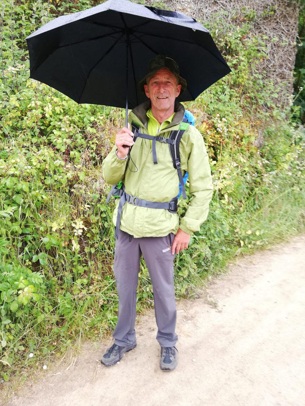 Willi mit Schirm und ich im Poncho.