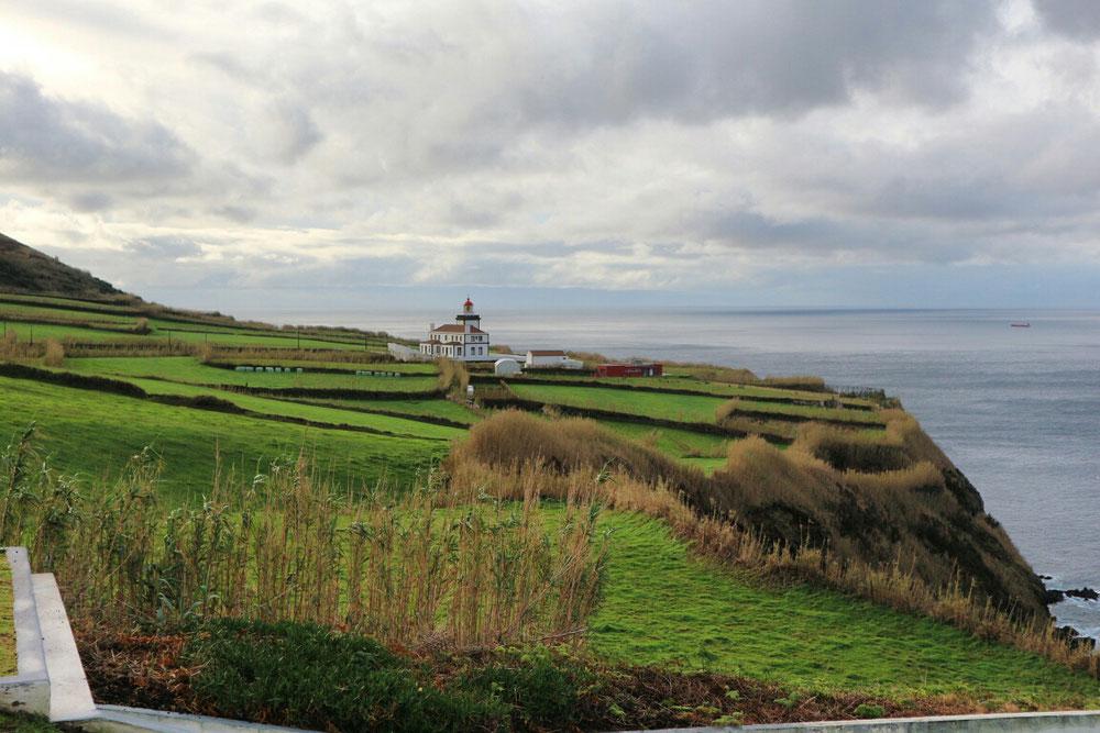 Der Leuchtturm von Ginetes umgeben von sattgrünen Wiesen und dem Atlantik