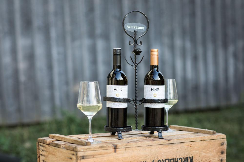 Flaschen vom Weingut Heiß und mit Wein gefüllte Gläser auf einer Holzkiste