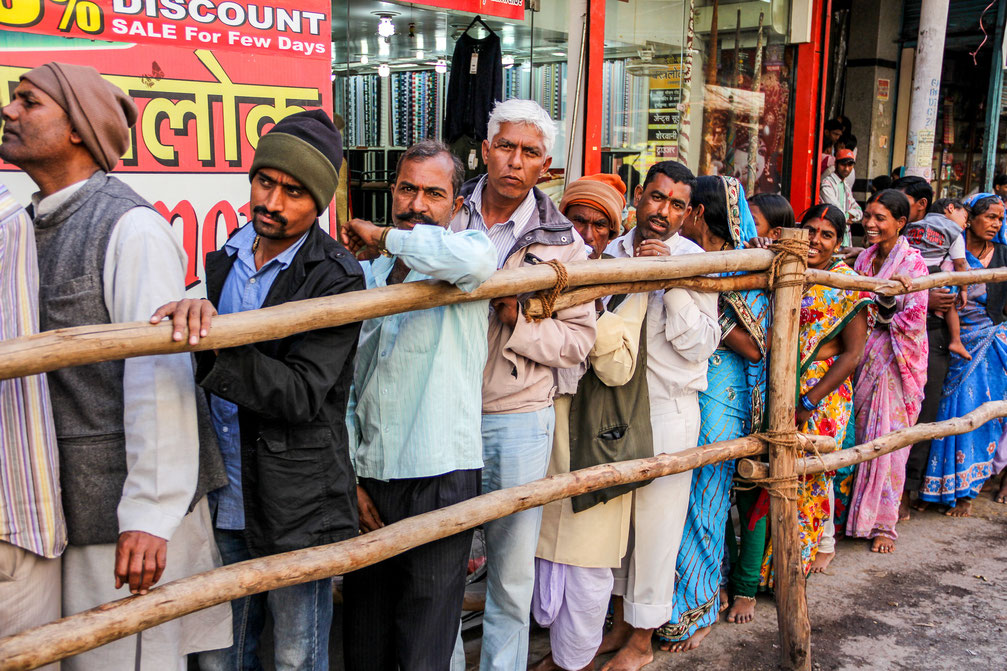People cuing behind a fence in Varanasi, India