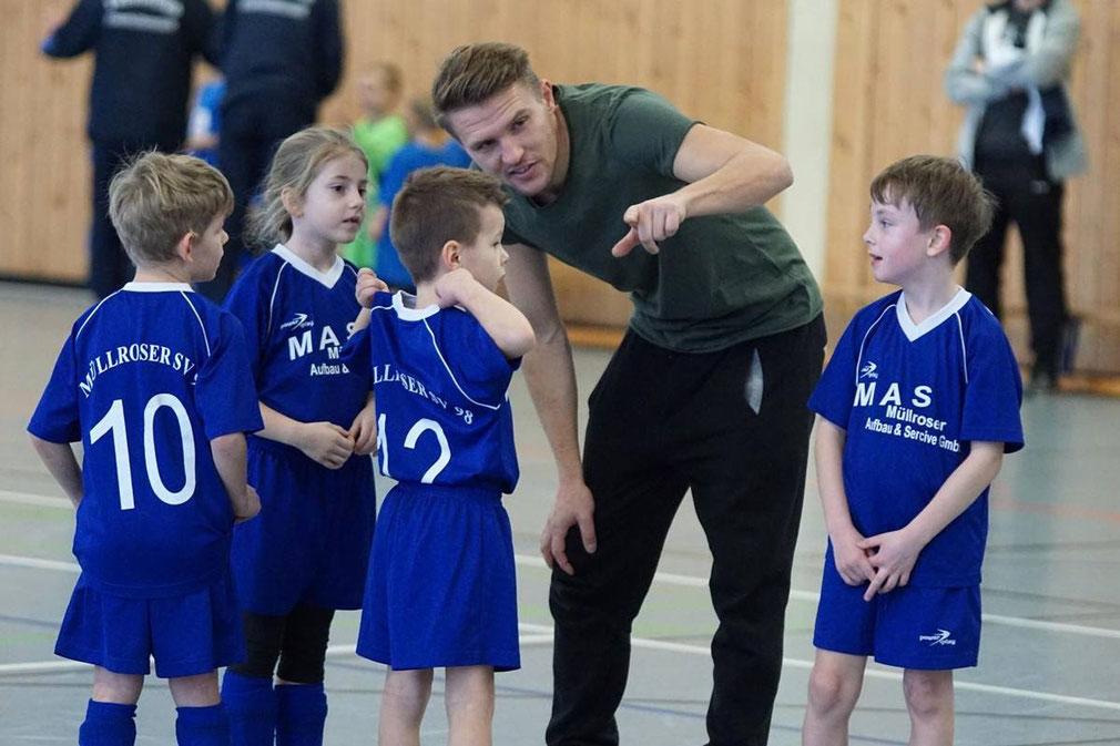 Foto: Kenny Fuhrmann - Spieler der Ü35 und Trainer bei den ganz kleinen! Tino Heering erklärt seiner F-Jugend das Spiel mit dem Ball.
