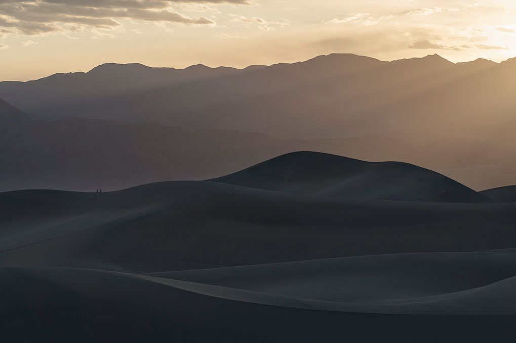 A couple enjoying the sunset on sand dunes, Stovepipe Wells, Death Valley National Park, California USA, 1280x853px