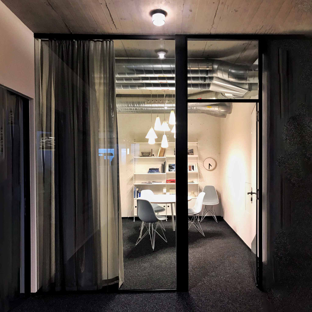 Sitzungszimmer im Stile einer kleinen Bibliothek. String Regal, Hat Tisch und Vitra Stühle. Hinter Glasfront gebaut.