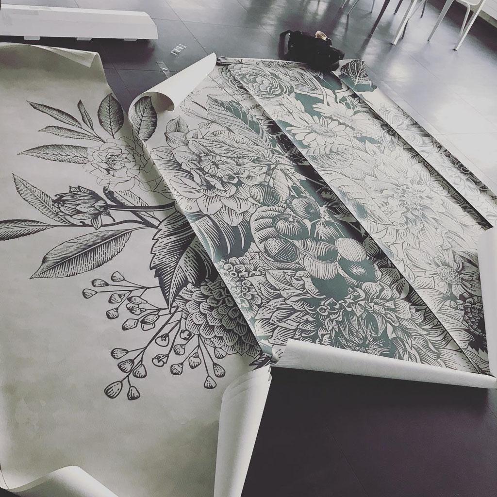 Tapetenbahnen liegen auf dem Boden Ausgebreitet. Grafisch umgesetztes Pflanzen-Muster mit Blättern, Blüten und Früchten in Grün auf Beige.