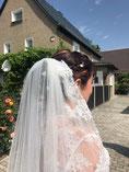 Ansicht einer Braut mit weißem Schleier über der Hochsteckfrisur in einer Einfahrt, Halbprofil von hinten.