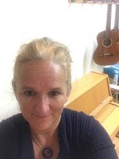 Andrea Schilling guckt in die Kamera, hinter hier sieht man ein Holzklaiver und eine Gitarre an der Wand hängen.