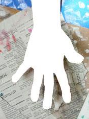 Foto von einer Kinderhand über Zeitungspapier. Da die Hand aus dem Bild mit einem Bearbeitungssystem rausgeschnitten, aber nichts dafür eingesetzt wurde ist über den Zeitungen, mit Farbkleksen, nur der Umriss einer Hand zu sehen.