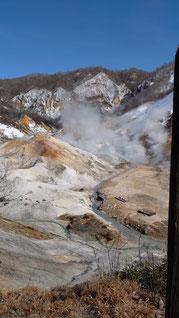 活火山の火口から白い煙がもくもくあふれている
