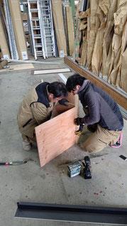 木の型に土台水切りを取り付けているスタッフとそれを指導するスタッフ
