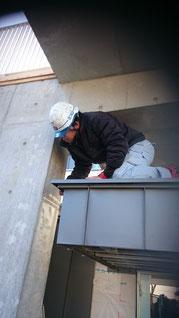 立平の屋根を外壁にはろうと屋根の上にしゃがんでいるスタッフ