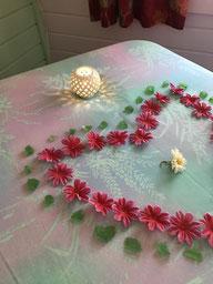 Photo du haut de la table de massage décorée avec un coeur de fleurs fuschia bordées de pierre émeraude