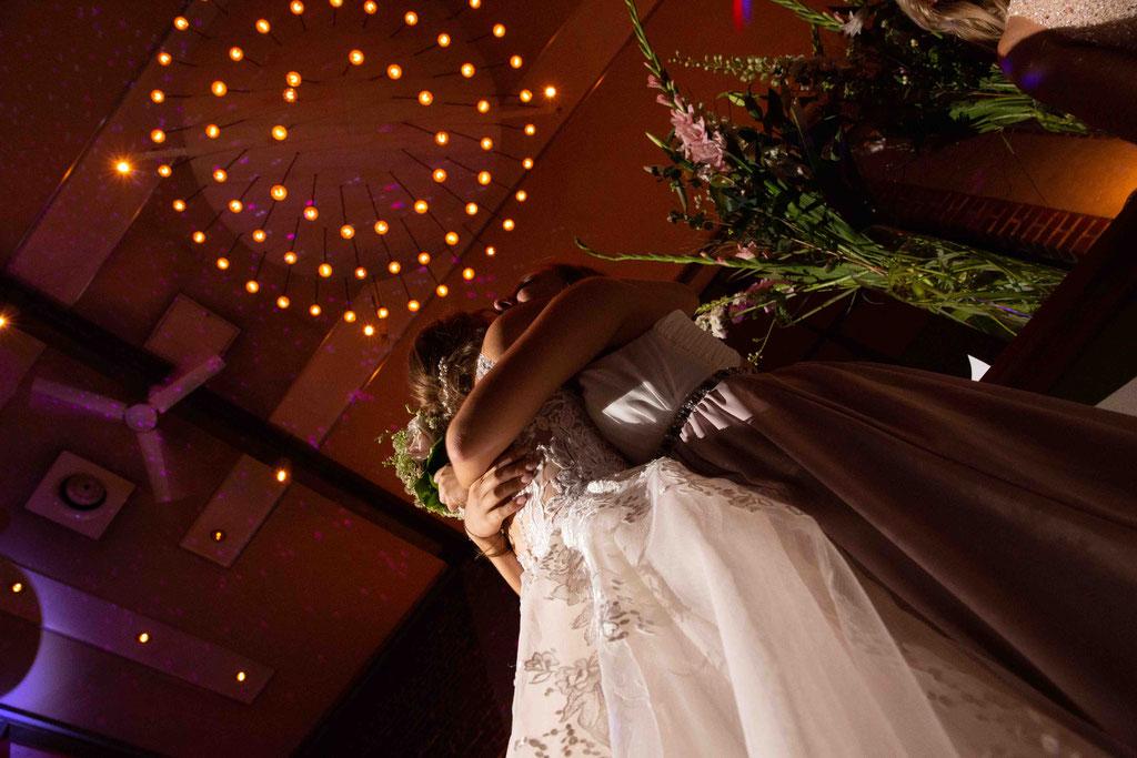 Hochzeit: Weststadtbar Darmstadt, Mainzer Straße 106, 64293 Darmstadt - Hochzeitsfotograf, Umarmung der Braut, Brautjungfer, Hochzeitsgäste in der Weststadtbar Darmstadt
