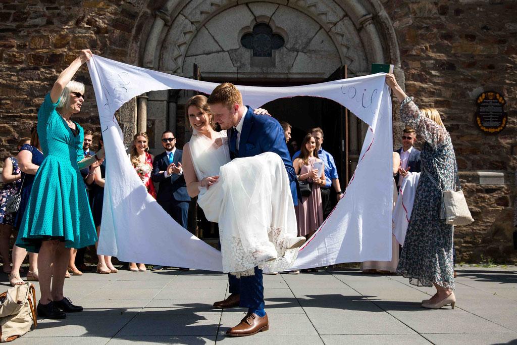 Durchs Herz heben Hochzeitsbrauch, Brauch zur Hochzeit Herz ausschneiden, Hochzeitsbilder vor der Kirche