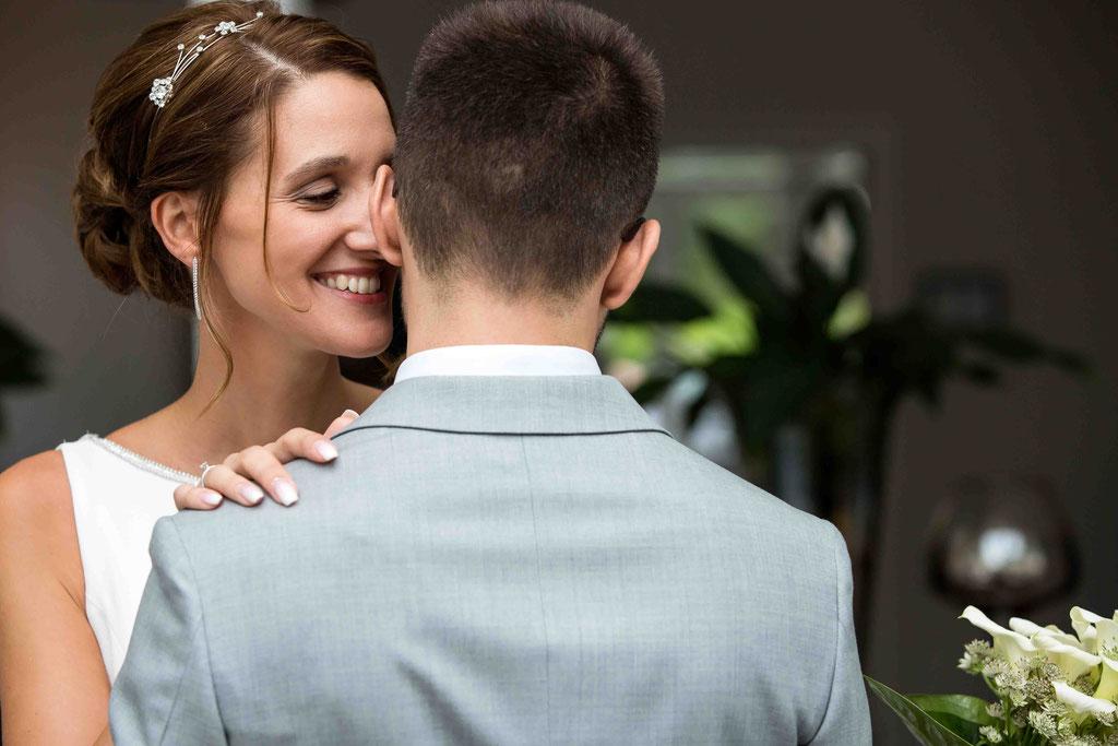 Braut flüstert dem Bräutigam etwas ins Ohr, Geheimnisse beim Brautpaar, Hochzeitsfoto Ideen