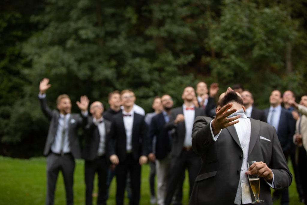 Wurf des Brautstrauß an einer Hochzeit, Fang die Ansteckblume, Männer auf der Hochzeit, Hochzeitsbild