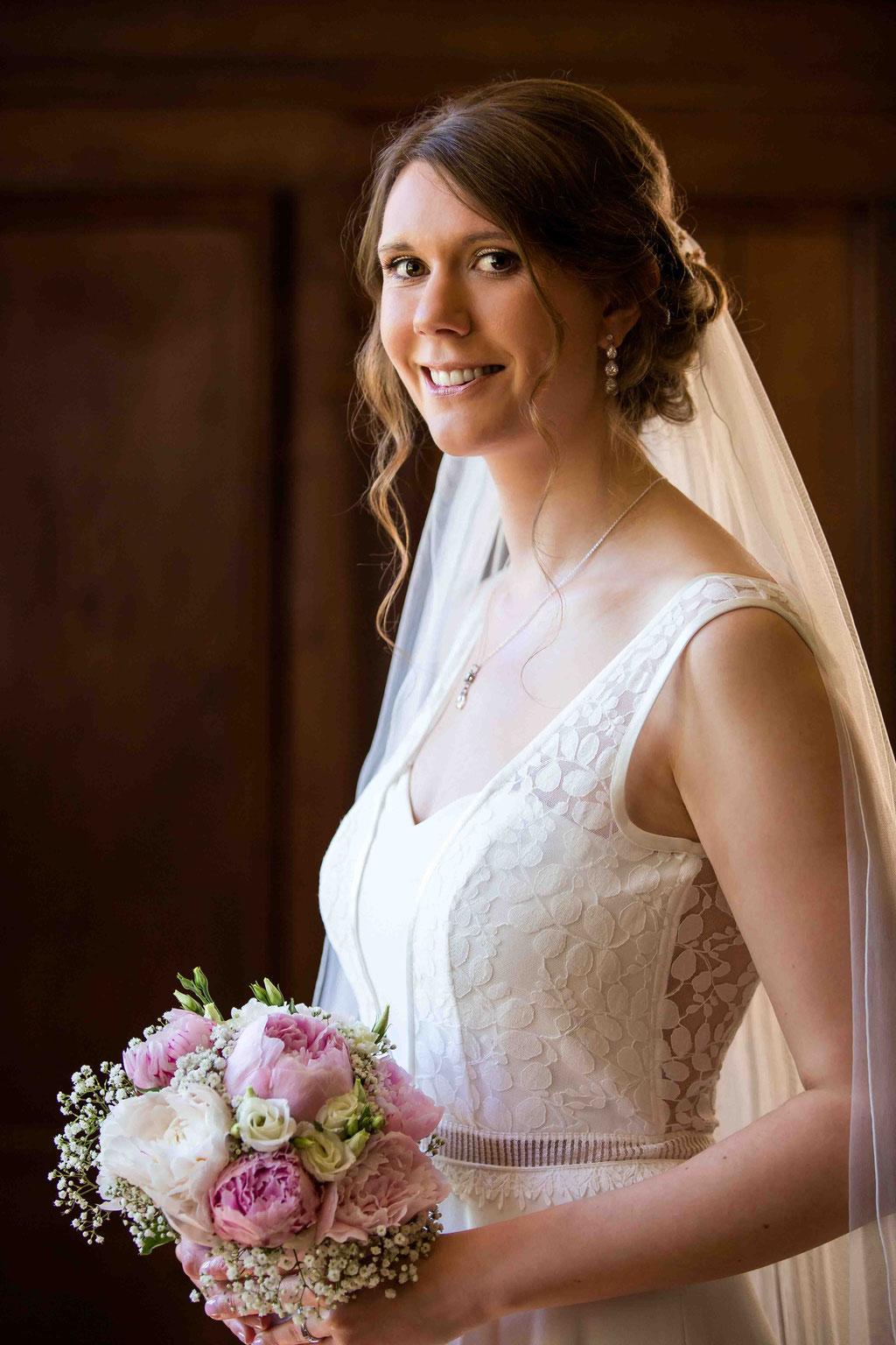 Porträt der Braut am Fenster, Brautkleid und Brautstrauß fotografiert vom Hochzeitsfotograf