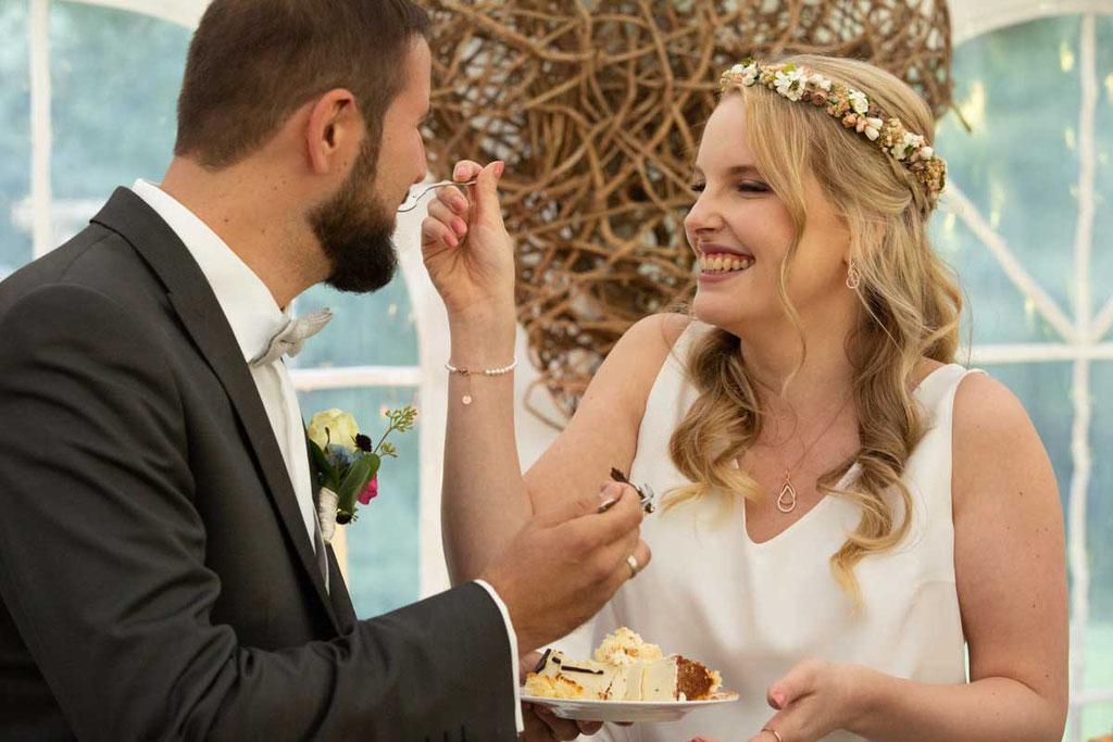 Hochzeitstorte essen und sich gegenseitig füttern, hochzeitsbilder erstes Stück Hochzeitstorte