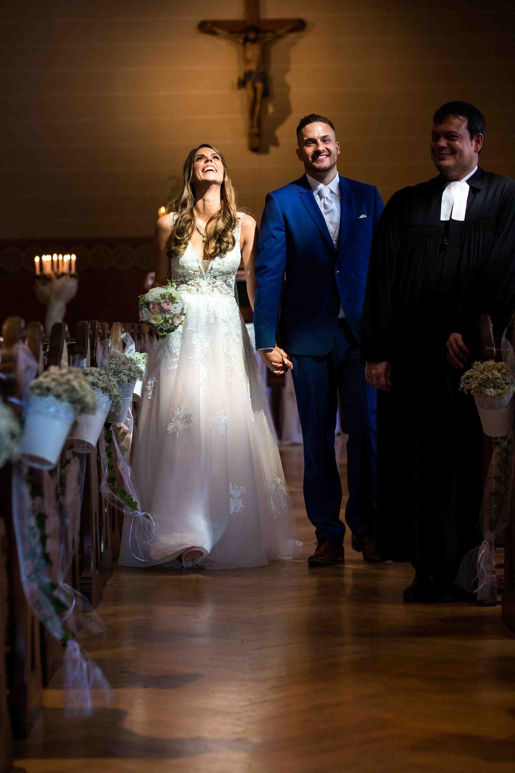 Auszug aus der Kirche, Lichtschein auf das Brautpaar, Braut lächelt, wundervolles Brautkleid