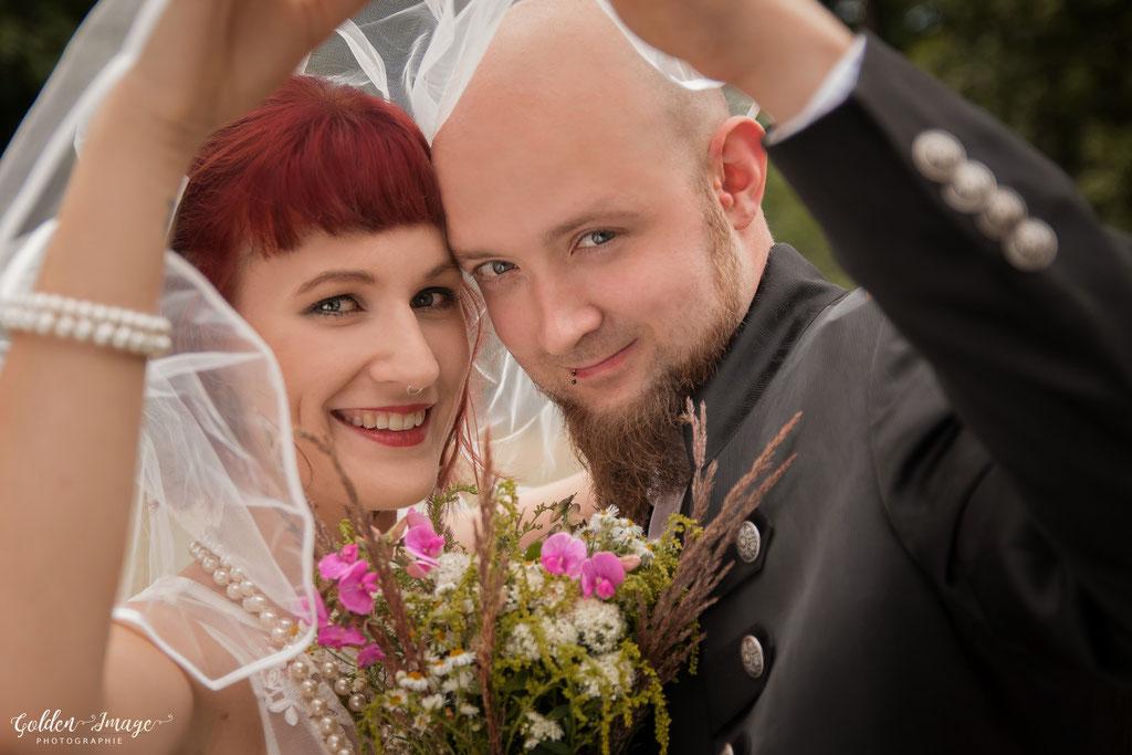 Das lächelnde Brautpaar unter dem Schleier