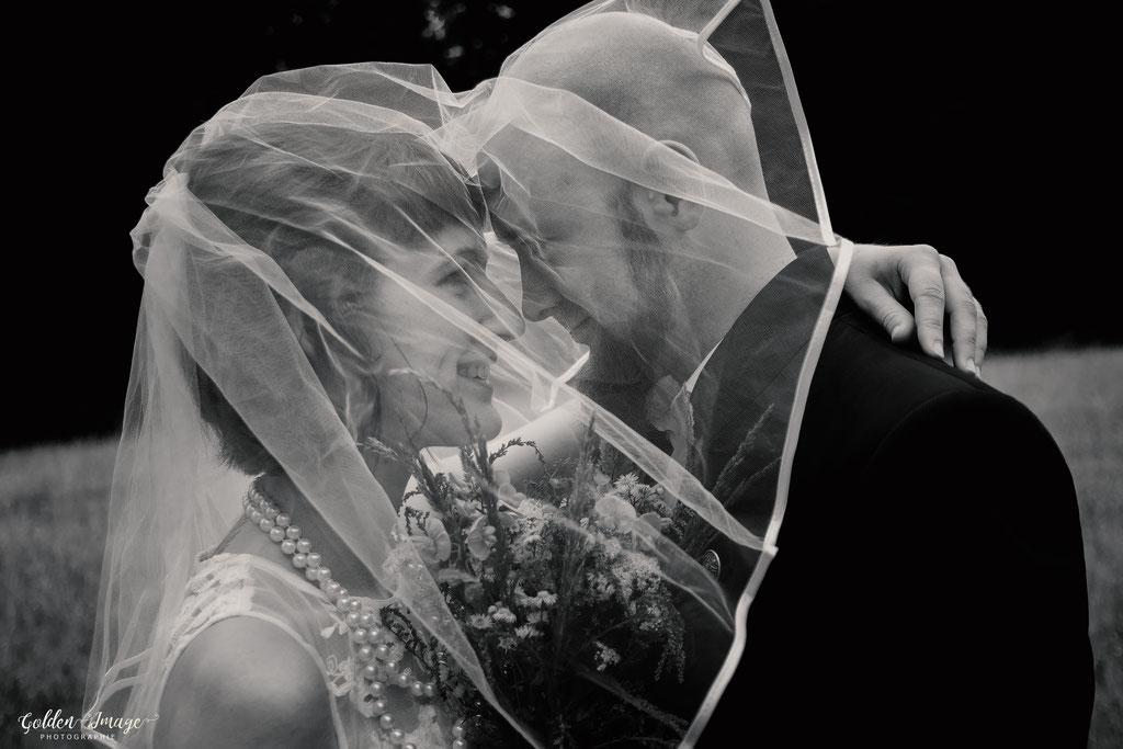 verliebtes Brautpaar unter dem Brautschleier