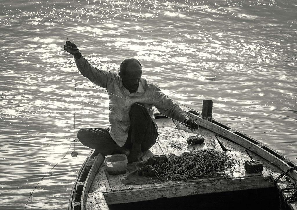 Ein Fischer bei der Arbeit bei Sonnenaufgang