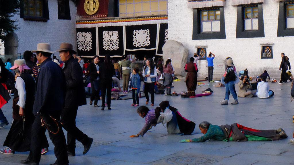Tibetische Pilger umrunden den Jokhang-Tempel in Lhasa mit rituellen Niederwerfungen