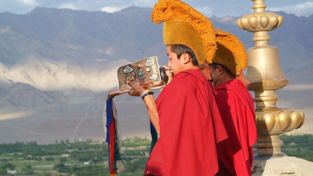 Zwei Mönche blasen mit den Muschelhörnern zum Morgengebet im Kloster Thikse