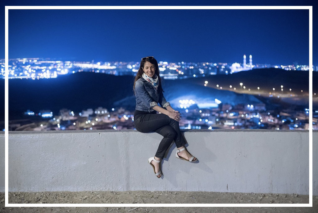 Irene enjoying the spectacular view to Muscat, Oman - by night