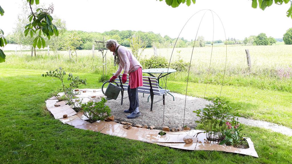 02.05. Doris giesst denn Karton nass, bevor er mit Rasenschnitt abgedeckt wird