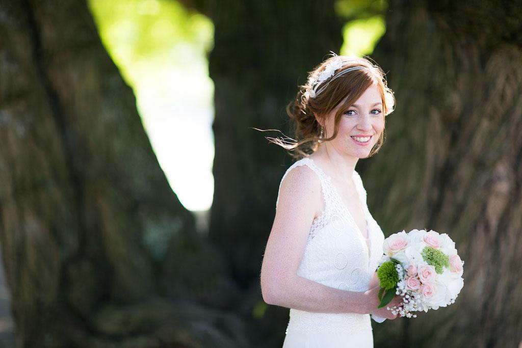 Braut mit Brautstrauß lächelt in die Kamera