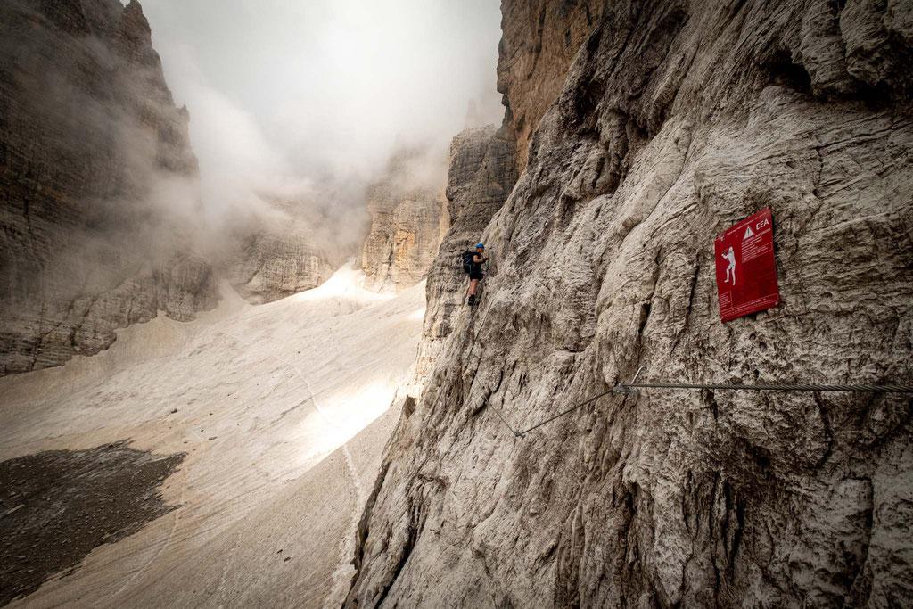 Descending on the via ferrata Brentari onto the remnants of the Vedretta di Ambiez