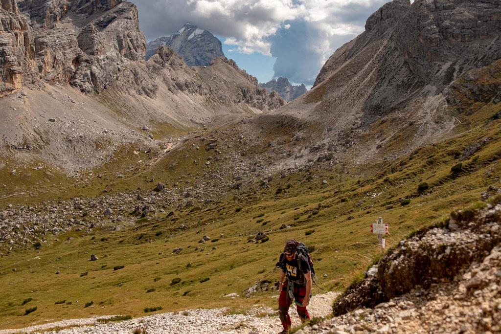 Grassy plateau with a sign for Bivacco Slataper. Visible in the far distance Forcella Grande (saddle Grande)
