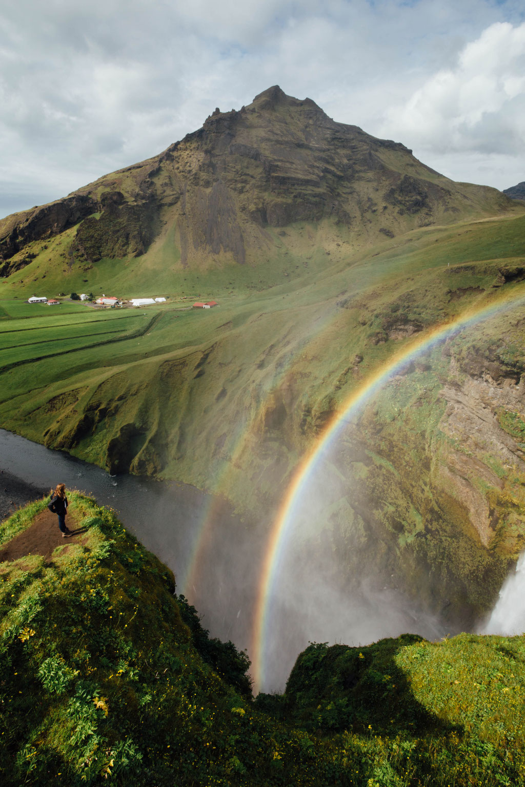 Rainbow created from the spray of Skogafoss. Road trip itinerary Iceland.