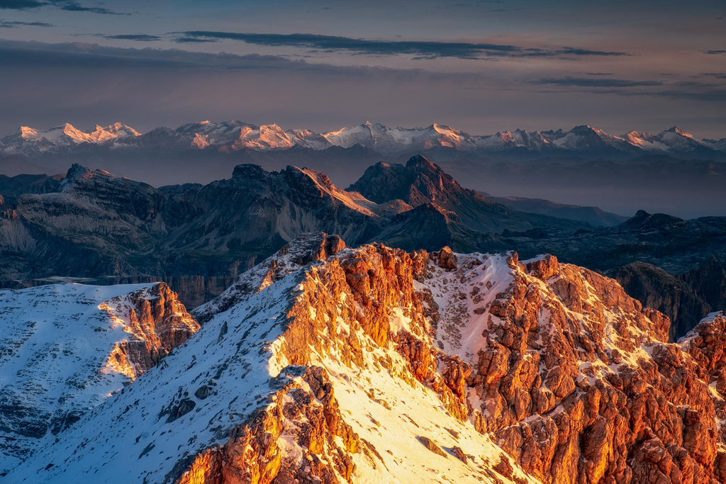 The first light on the easter slopes of the Piz Boé summit. Snowcapped Austrian alps can be seen in the distance
