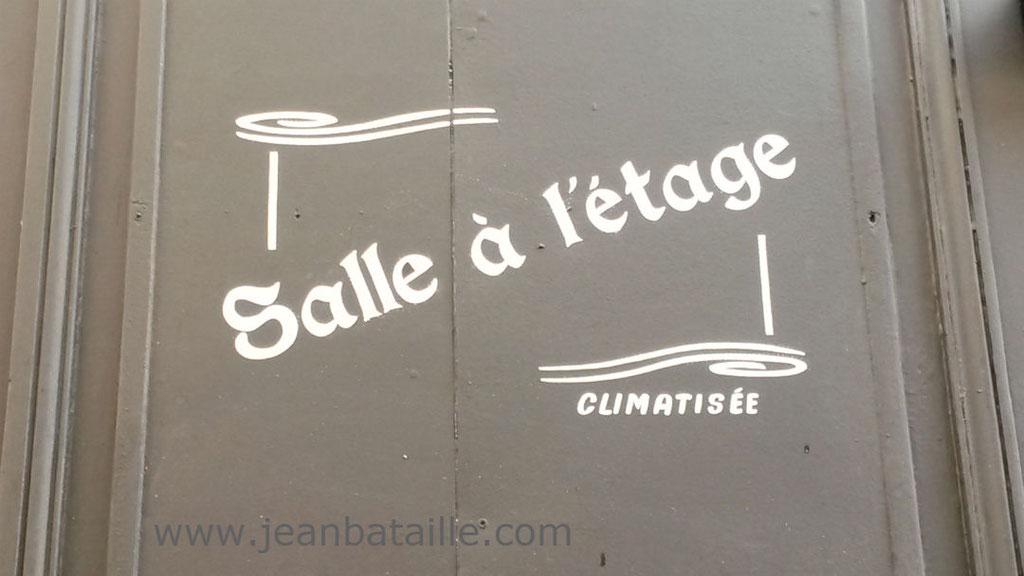 Lettres peintes en acrylique sur devanture magasin en bois