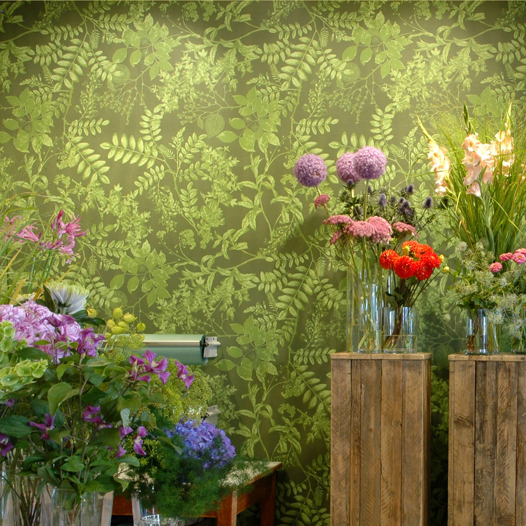 flowers in front of a wallpaper in green shades / Interior design for shops