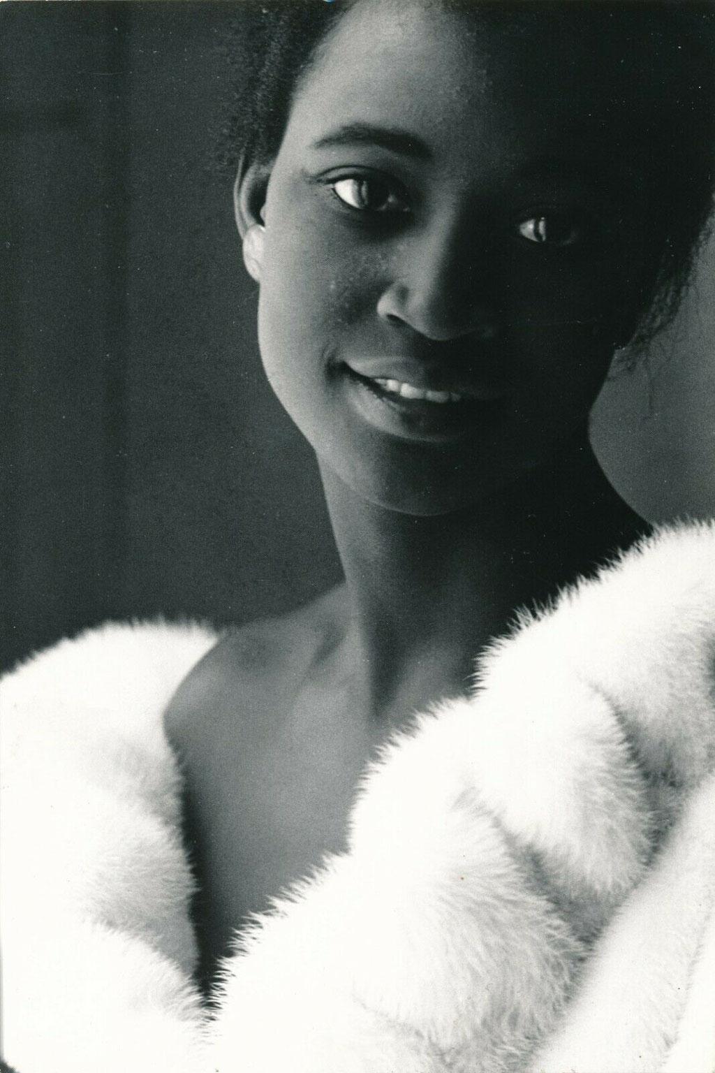 photographie femme noir à la fourrure blanche