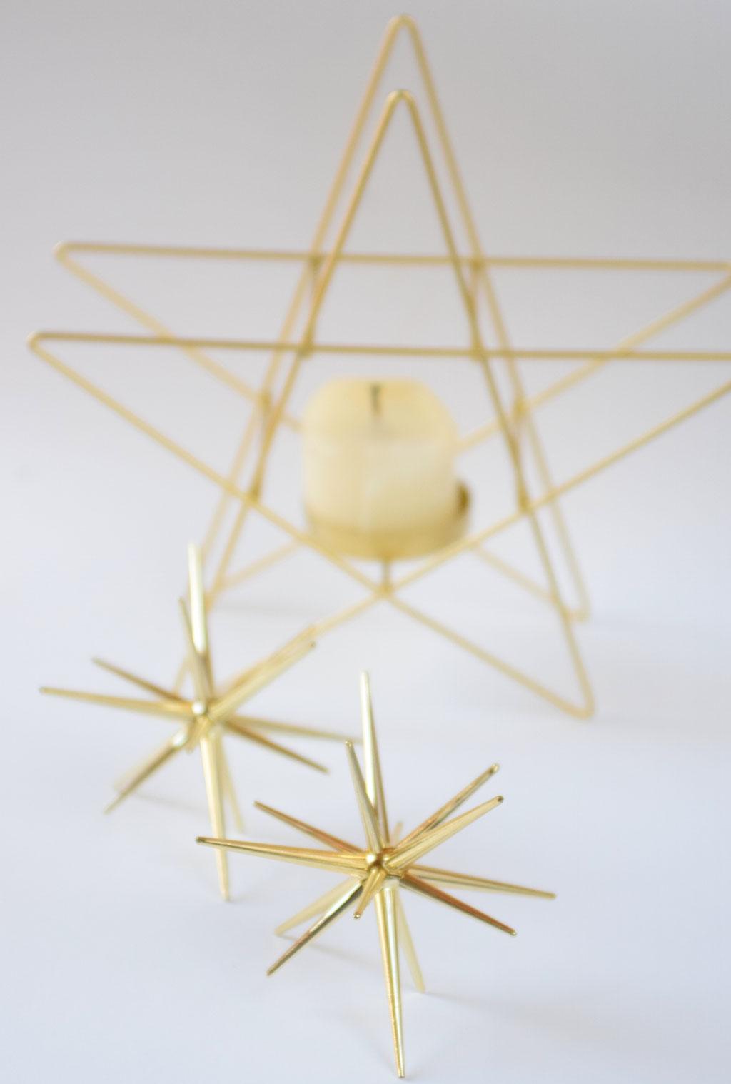 Goldene Highlights für weihnachtliche Dekoration mit Sternen und Kerzen.